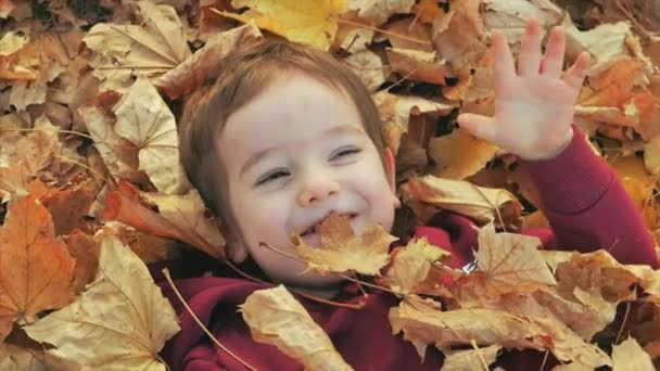 Children play in the park, throw yellow autumn leaves at a smiling boy, a happy baby lies in autumn leaves, happy emotions. The concept of happy childrens emotions.