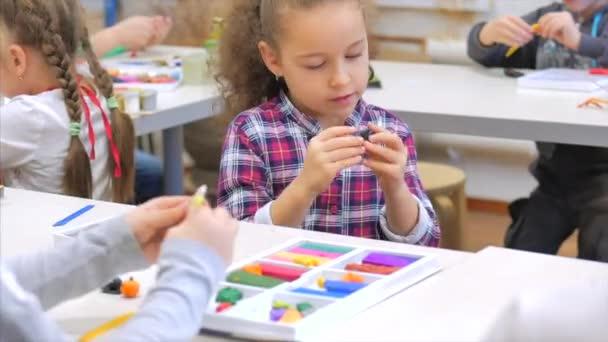 Dětské ruce, detailní záběry dětí, sochy z plastu u stolu, dětské vývojové kruhy pro kreslení a sochařství. Vývojový proces u dětí od 5 do 7 let.