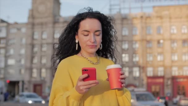 Woman Young Muslim Walking in the City Center, Using Smartphone and Drinking Coffee. Concept Communication, online shopping, Good Mood, Positive Emotions.