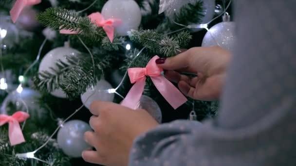 Női kezek közelről, kezek díszítik a karácsonyfát újévi játékokkal. Karácsonyi dekorációk, labdák, fények, koszorúk, lógj a karácsonyfán.
