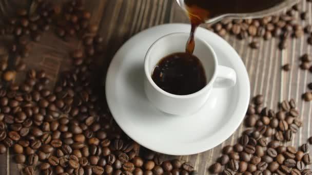 Šálek kávy a kávová zrna. Bílý šálek odpařené kávy na stole s praženými fazolemi. Pomalý pohyb káva pour.