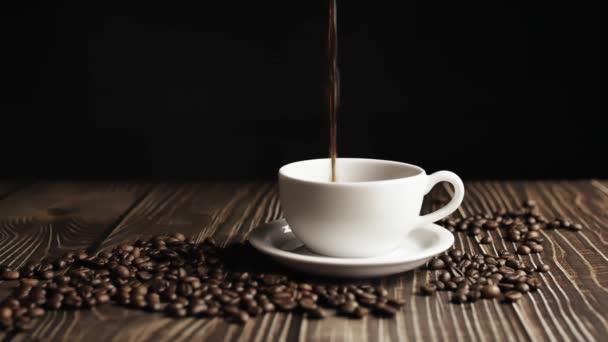 Kávécsésze és kávébab. Fehér csésze elpárolgó kávé az asztalon pörkölt babbal. Lassú Motion kávé öntés.