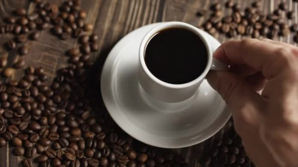 Male Hand takes a mug of coffee.Coffee cup and coffee beans. White cup of steaming coffee on the table with roasted bean.