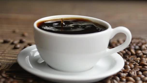 Egy fából készült asztalon egy fehér bögre kávé és kávébab heverészik, közelről egy csésze kávéba zuhanó kávécseppek..