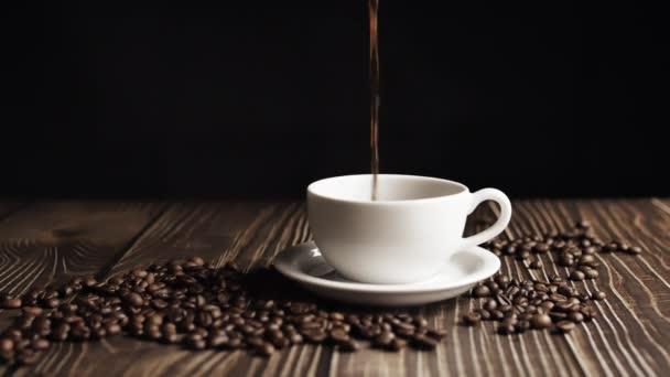 Moziba megyünk. Kávécsésze és kávébab. Fehér csésze elpárolgó kávé az asztalon pörkölt babbal. Lassú Motion kávé öntés.