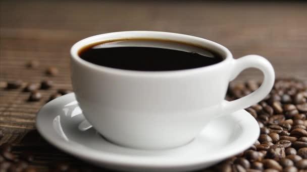 Na dřevěném stole leží bílý hrnek kávy a kávových zrn, zblízka kapky kávy padají do šálku.