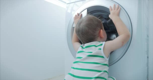 Cute Little Boy Looks Inside the Washing Machine. Cylinder Spinning Machine. Concept Laundry Washing Machine, Industry Laundry Service.