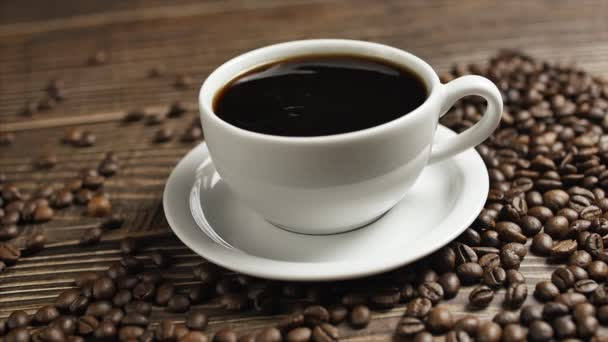 On a wooden table is a white mug of coffee and coffee beans are lying around, close-up drops of coffee falling into a cup.