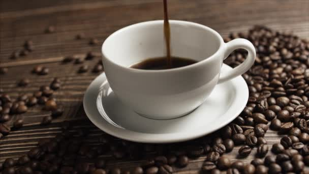 Coffee cup and coffee beans. White cup of evaporating coffee on the table with roasted bean. Slow Motion coffee pour.