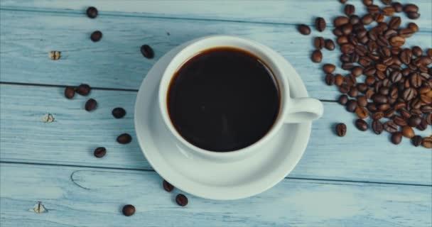 Top View Kávový pohár a kávová zrna. Bílý šálek odpařené kávy na stole s praženými fazolemi. Pomalý pohyb káva pour.