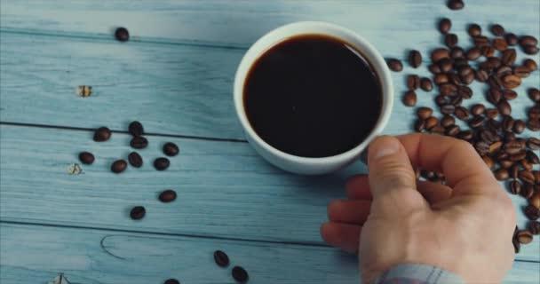 Mužská ruka si vezme hrnek kávy.Kávový šálek a kávová zrna. Bílý šálek kouřící kávy na stole s praženými fazolemi.