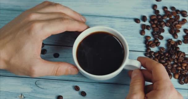 Férfi kéz vesz egy bögre kávét. Kávé csésze és kávébab. Fehér csésze gőzölgő kávé az asztalon pirított babbal.