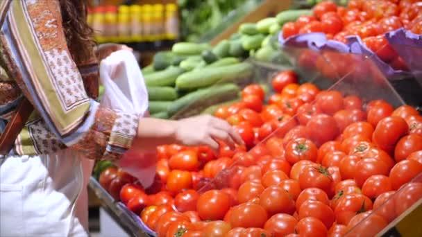 Hezká mladá žena nebo maminka nakupuje v supermarketu, vybírá výrobky v supermarketu pro vaření, zdravé potraviny, rajčata, avokáda, ovoce, pomeranče na trhu, supermarket.