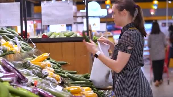 Pretty young woman or mother makes purchases in a supermarket, chooses food watermelon, avocado, fruits, carrots, cabbage, salad, cauliflower, meat, apples, tomatoes,oranges in the market,supermarket.