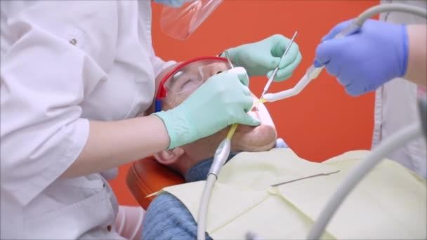 Person unterzieht sich einer ärztlichen Untersuchung und Behandlung der Mundhöhle beim Zahnarzt. Zahnärztin, die Zähne eines Mannes behandelt, der Patient in der Klinik ist. Zahnärztin bei der Arbeit.