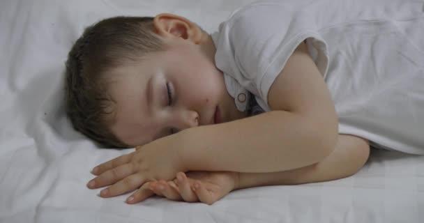 Roztomilý chlapeček spí sladce v posteli, koncepce dětského spánku.