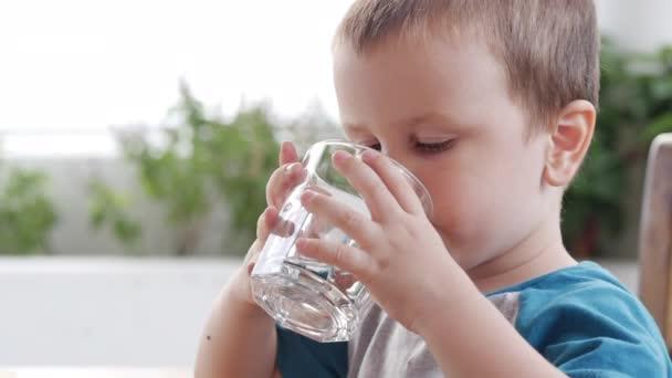 Roztomilý chlapeček pije sklenici vody v kavárně. Zpomal, malý chlapec pije vodu. Detailní záběr. To dítě pije šálek vody..