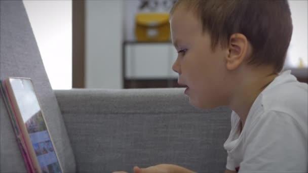Neugierige niedliche Vorschulkind Mädchen mit digitaler Tablet-Technologie Gerät allein auf dem Boden liegend. Kleines Kind hält Pad Computer Surfen im Internet spielen Spiel zu Hause. Suchtkonzept für Kinder