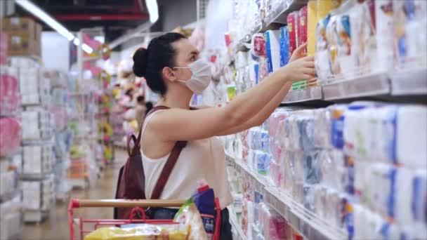 Mladá žena v masce před epidemií koronaviru stojí v supermarketu, kde lidé v panice kupují vše. Korontin, izolace lidí.
