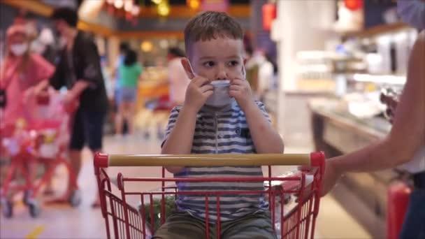 Rodina nakupuje v hypermarketu, dítě v ochranné masce před viry sedí v nákupním košíku sleduje videa na smartphonu. Lidé v ochranných maskách panikaří kvůli epidemii