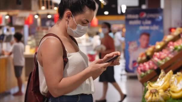 Junge Frau in Maske von einer Coronavirus-Epidemie kauft im Supermarkt ein, tippt auf ihr Smartphone, Menschen, die in Panik vor der globalen Epidemie alles kaufen. Corontin, epidemische Isolation