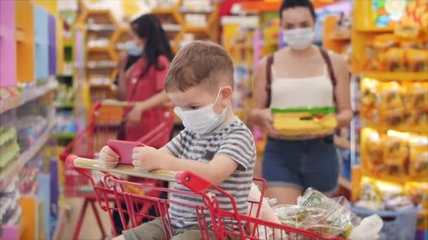 Máma s dětmi nakupuje v hypermarketu, dítě sedí v ochranné masce před viry, sleduje videa na smartphonu.