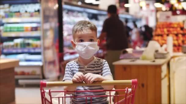 Dítě v masce z epidemie koronaviru nebo virů sedí v nákupním vozíku a čeká na rodiče, kde lidé všechno zpanikařili, jídlo, oblečení.