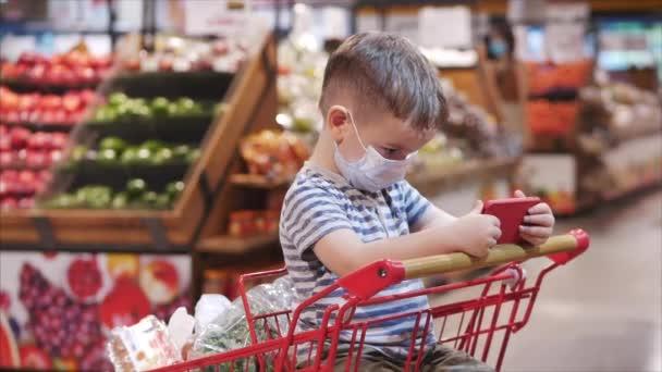 Mutter mit Kindern kauft im Supermarkt ein, das Kind sitzt in einem Einkaufswagen mit Produkten und guckt Cartoons auf dem Smartphone.