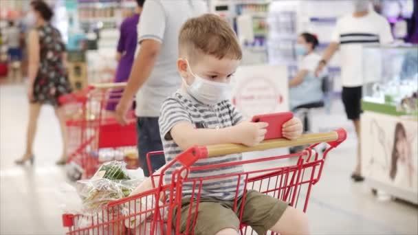 Familie kauft im Supermarkt ein, das Kind sitzt in einer Schutzmaske vor Viren, schaut Videos auf dem Smartphone.