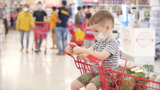 A család a hipermarketben vásárol, a gyermek vírusoktól védő maszkban ül, videókat néz az okostelefonon.