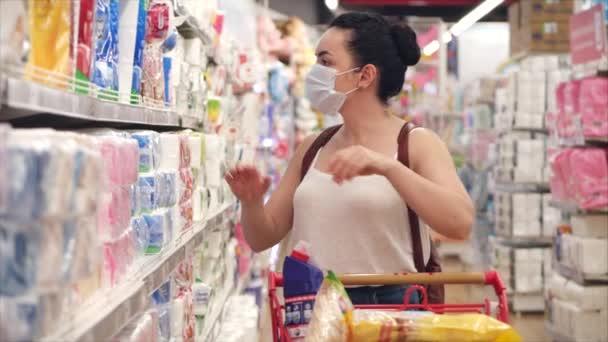Junges Mädchen oder Frau in einer Maske von Coronavirus-Epidemie kauft Toilettenpapier im Supermarkt, wo Menschen in Panik alles kaufen, einkaufen im Geschäft, um die Quarantäne zu überstehen.Corontin, Isolation von Menschen.