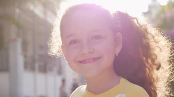 Vidám, vicces kislány mosolyog, az utcán a kamerába néz, egy aranyos gyerek játszik az utcán, rajzokat készít az öröm színes krétáival, egy óvodás gyönyörű mosollyal.