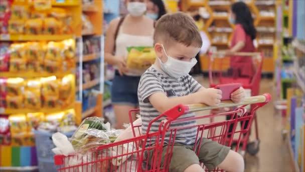 Familie kauft im Supermarkt ein, Kind sitzt in Schutzmaske vor Viren, Kind sitzt im Einkaufswagen, sieht Videos, Zeichentrickfilme am Telefon. Konzeptmenschen, Coronavirus, Epidemie.