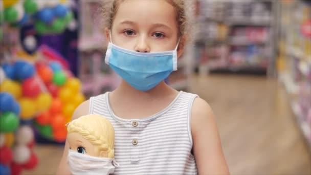 V obchodě Roztomilá holčička v masce před viry koronavirové epidemie podívá se do kamery drží panenku ve svých rukou na panence jako prostředek ochrany masky před viry, maskované