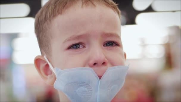 Portrét roztomilého chlapečka v masce z virů epidemie koronaviru v obchodě s rodičem, pláče vyděšeně křičí, utírá si oči rukama, dítě se rozhlíží kolem
