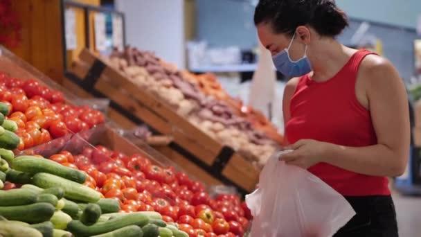 Mladá žena v masce před epidemií koronaviru stojí v potravinářském oddělení supermarketu. Rychle kupuje jídlo, kde lidé v panice nakupují jídlo..