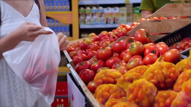 Woman is making purchases in the supermarket, choosing products at the supermarket for cooking, healthy foods, tomatoes, avocados, fruits, oranges at the market, supermarket.