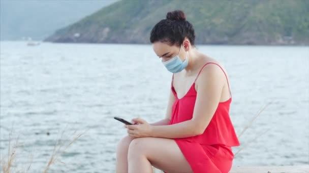 Junge Frau in Maske von der Coronavirus-Epidemie sitzt einsam am Ufer am Meer, tippt auf ihr Smartphone, Konzept von Menschen, die sich vor Panik über die globale Epidemie selbst isolieren.