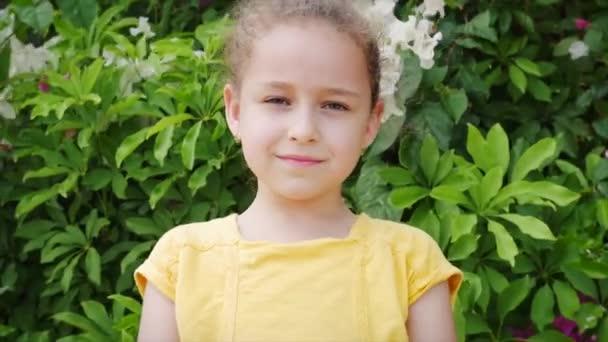 Portré Vicces kislány mosolyog, nézi a kamerát az utcán, egy aranyos gyerek játszik az utcán, rajzokat készít színes krétákkal az öröm, egy óvodás egy gyönyörű mosollyal.