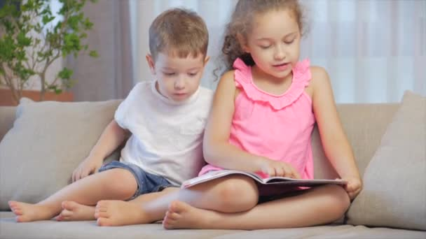 Cute children,sister with a younger brother, looking at a book magazine textbook dictionary tablet read fairy tales, kids are reading books sitting on the couch,preschool and school education.
