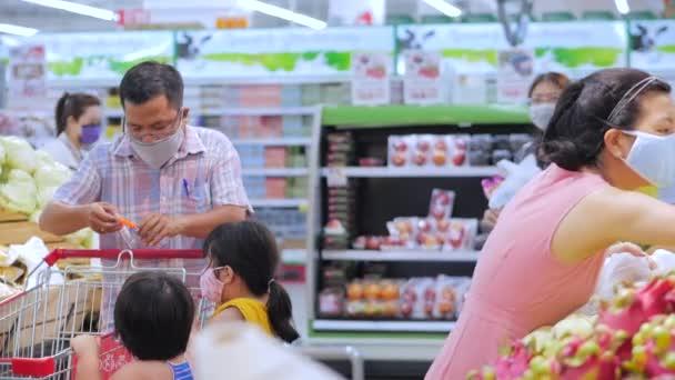Ältere junge Menschen, Frauen und Männer, alte Menschen und maskierte Kinder gegen eine Pandemie asiatisch-europäischen Aussehens in den Supermärkten tätigen massive Einkäufe. Han Hoa Provinz, Vietnam 20. April 2020.Covid-19