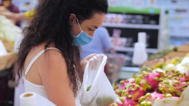 Eine junge Frau mit einer Maske vor einer Coronavirus-Epidemie steht in der Lebensmittelabteilung eines Supermarktes. Sie kauft schnell Lebensmittel ein, wo die Menschen in Panik Lebensmittel kaufen.