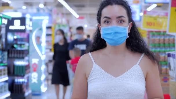 Porträt einer Europäerin in einer Maske von einer Coronavirus-Epidemie kauft im Supermarkt ein, wählt Toilettenpapier, Menschen in Panik vor der globalen Epidemie kaufen alles Covid-19,