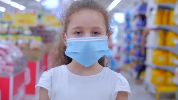Roztomilá holčička z epidemie koronavirů nebo virů se dívá do kamery mezi maskovanými lidmi z viru, kteří nakupují v panice. Korontin, izolace lidí.