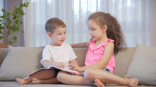 Roztomilé děti, sestra s mladším bratrem, při pohledu na knihu časopis učebnice slovník tablet číst pohádky, děti čtou knihy sedí na gauči, školka a školní vzdělávání.