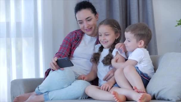 Šťastná rodina, maminka a roztomilé malé děti, matka si hraje s dětmi doma relaxaci pomocí chytrého telefonu mazlení sedět na pohovce dcera a syn se zasmějí, sledovat vtipná videa, bavte se, užijte si rodinné chvíle