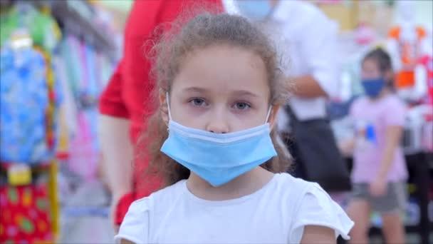 Maskované dítě z epidemie koronavirů nebo virů se dívá na kameru uprostřed maskovaných lidí z viru, kteří nakupují v panice.