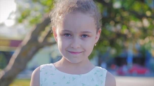 Portrét Legrační holčička se usmívá, krásný úsměv, na slunném letním dni, roztomilé dítě tvář dívá na kameru na ulici.