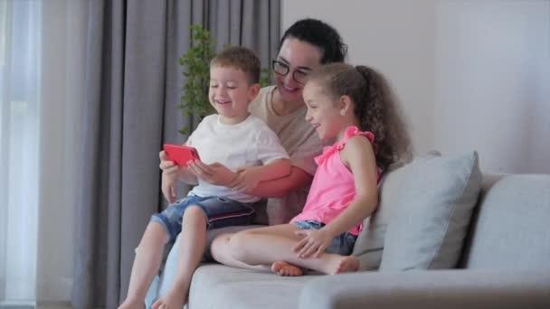 Glückliche Familie, Mutter und süße kleine Kinder, Mutter spielt mit Kindern zu Hause entspannt mit einem Smartphone kuscheln sitzen auf Sofa Tochter und Sohn lachen, lustige Videos ansehen, Spaß haben, Familienleben genießen Momente