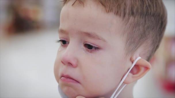 Portrét rozčileného uslzeného roztomilého chlapečka v masce z epidemických virů koronaviru, dítě nechce nosit masku, otírá si oči rukama, vystrašeně se rozhlíží, dítě se rozhlíží